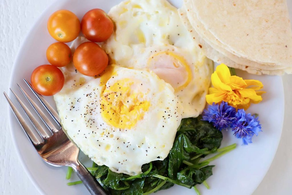 fried eggs, fruit, and greens